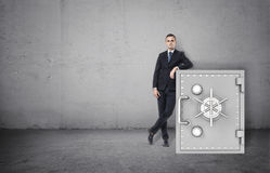 Businessman in confident pose standing next to the safe Royalty Free Stock Image