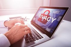 Businessman Configuring Privacy Settings In A Laptop. Close-up Of A Businessman`s Hand Configuring Privacy Settings In A Laptop royalty free stock photo