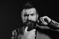 Businessman with confused face on dark red background. Man with long beard holds steel scissors. Macho in formal suit holds and cuts beard and moustache royalty free stock photography