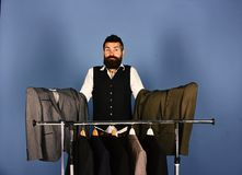 Businessman with confused face holds grey suits near jackets. On blue background. Shop assistant makes choice near clothes hangers. Business fashion and royalty free stock image