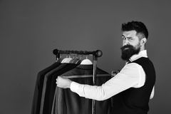 Businessman with confused face near jackets on blue background.Man with beard in vest by clothes rack. Fashion choice. Fashion choice concept. Businessman with stock photo