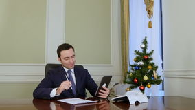 Businessman congratulates business partners with Christmas via internet with tablet stock video footage