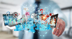 Businessman connecting devices and business objects together 3D. Businessman on blurred background connecting devices and business objects together 3D rendering Royalty Free Stock Image