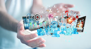 Businessman connecting devices and business objects together 3D. Businessman on blurred background connecting devices and business objects together 3D rendering Royalty Free Stock Images