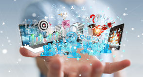 Businessman connecting devices and business objects together 3D. Businessman on blurred background connecting devices and business objects together 3D rendering Stock Photos