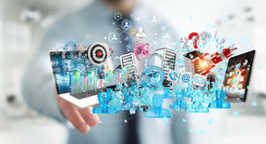 Businessman connecting devices and business objects together 3D. Businessman on blurred background connecting devices and business objects together 3D rendering Stock Images