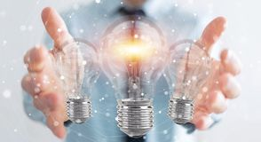 Businessman connecting modern lightbulbs with connections 3D ren. Businessman on blurred background connecting modern lightbulbs with connections 3D rendering Royalty Free Stock Photo