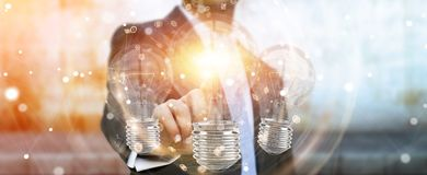 Businessman connecting modern lightbulbs with connections 3D ren. Businessman on blurred background connecting modern lightbulbs with connections 3D rendering Royalty Free Stock Photography