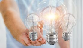 Businessman connecting modern lightbulbs with connections 3D ren. Businessman on blurred background connecting modern lightbulbs with connections 3D rendering Royalty Free Stock Images