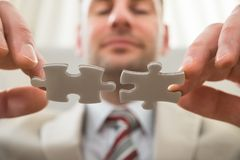 Businessman connecting together puzzle Stock Images