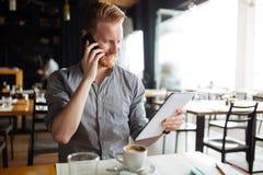 Businessman constantly working. Handsome smart businessman constantly busy and working royalty free stock image