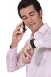 Businessman consulting his watch Stock Photography