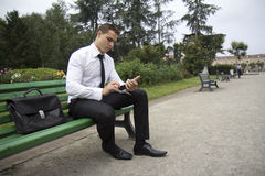 Businessman consulting a mobile phone. Young business man sitting on a bench outdoors. He is consulting a mobile phone royalty free stock photo