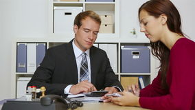 Businessman consulting woman in office stock footage