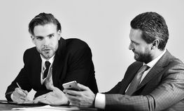 Businessman consults with financial analyst. Brainstorm business strategy concept. Business people hold smartphone, pen. And notebook. Managers with thoughtful stock images