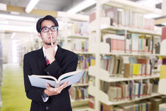 Businessman contemplating at library. Businessman is contemplating while holding book in a library Royalty Free Stock Photos
