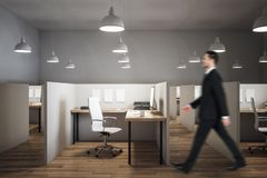 Businessman in contemporary coworking office. Side view of young businessman walking in contemporary coworking office interior with lamps and furniture royalty free stock images