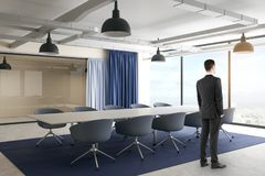 Businessman in contemporary meeting room. Side view of thoughtful young businessman standing in contemporary meeting room interior with furniture, curtains and royalty free stock photo