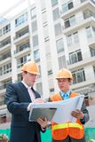Businessman and contractor. Businessman showing contractor the plan of the building Stock Images