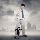 Businessman controlling his subordinate. Businesswoman hanging on string and controlled by a businessman Royalty Free Stock Images