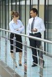 Businessman conversing with businesswoman at corridor Stock Image