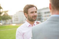Businessman conversing with colleague at park on sunny day Stock Image