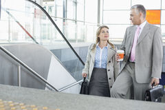 Businessman conversing with female colleague while walking up stairs in train station Royalty Free Stock Images