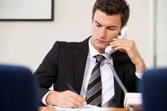 Businessman conversing on landline phone while writing on paper Stock Photography