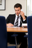 Businessman conversing on landline phone while writing on paper Stock Photo