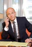 Businessman conversing on mobile phone, looking up Royalty Free Stock Images