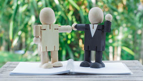 Businessman cooperate. Wooden doll of businessman have a deal on notebook, business concept stock photography