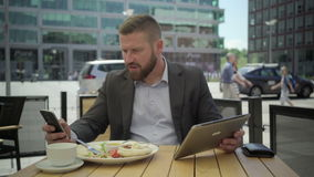 Businessman copy data from tablet to smartphone, during lunch, steadicam. stock video footage