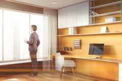 Man in yellow and gray home office with window. Businessman in corner of modern home office with yellow and gray walls, large window and long computer table with royalty free stock photography