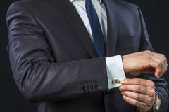 Businessman correcting cufflinks Royalty Free Stock Photos