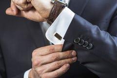 Businessman correcting cufflinks Stock Photo