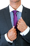 Businessman correcting a tie. On black background Stock Images