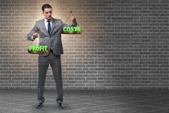 The businessman in cost benefit balance concept. Businessman in cost benefit balance concept stock image