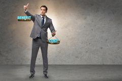 The businessman in cost benefit balance concept. Businessman in cost benefit balance concept stock photos