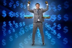 The businessman in cost benefit balance concept. Businessman in cost benefit balance concept stock photography