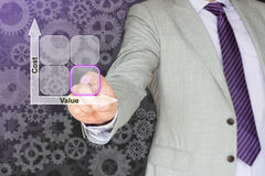 Businessman with cost value matrix. Businessman in a grey suit taps on the square with the lowest cost and the highest value in a cost-value matrix Stock Images