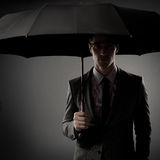 Businessman in costume holding black umbrella Stock Photo