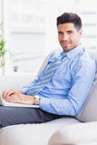 Businessman on couch using his laptop smiling at camera Stock Image