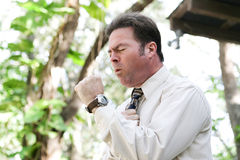 Businessman Coughing with Flu. Businessman coughing from the flu, a cold, or other illness, in outdoor environment Stock Photo