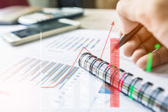Businessman count money coin with calculator business graphs and charts report on tabble, calculator on desk of financial planing. Stock Photo