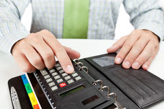 Businessman counting on calculator. Royalty Free Stock Photo