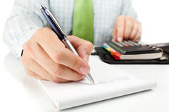Businessman counting on calculator. Royalty Free Stock Images