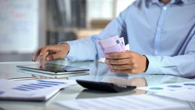 Businessman counting euro and planning company budget by tablet application stock photography