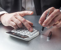 Businessman counting his financial margin with calculator Stock Photos