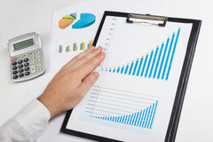 Businessman counting losses and profit working with statistics, analyzing financial the results on white background Stock Photos