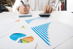 Businessman counting losses and profit working with statistics, analyzing financial the results on white background Royalty Free Stock Photos
